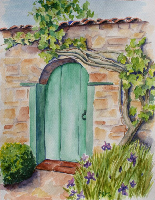 Beautiful home-gate in Monterey, California. Turquoise door in a rock wall with plants and a tree in front